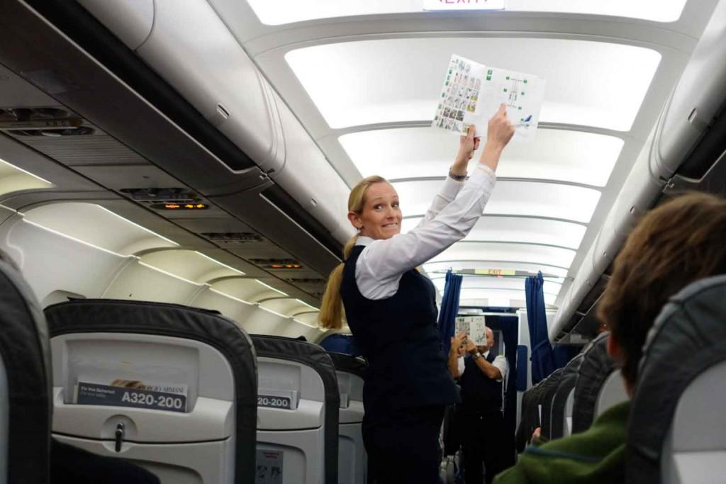 Stewardess mit Sicherheitsblatt